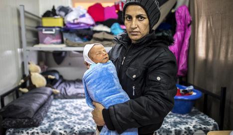 Una madre cuida de su bebé recién nacido en uno de los barracones del centro de tránsito de refugiados al norte de Macedonia. EFE